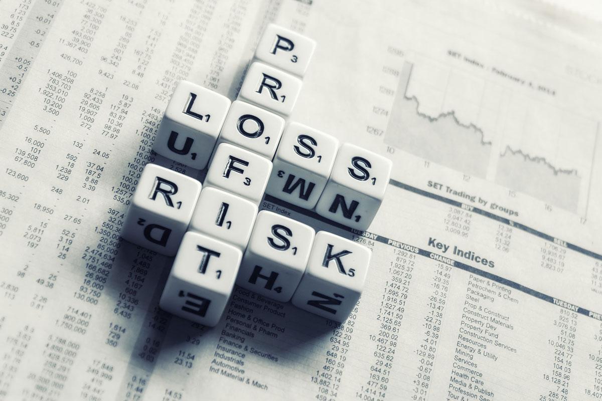 dice on financial newspaper spelling profit, loss, risk