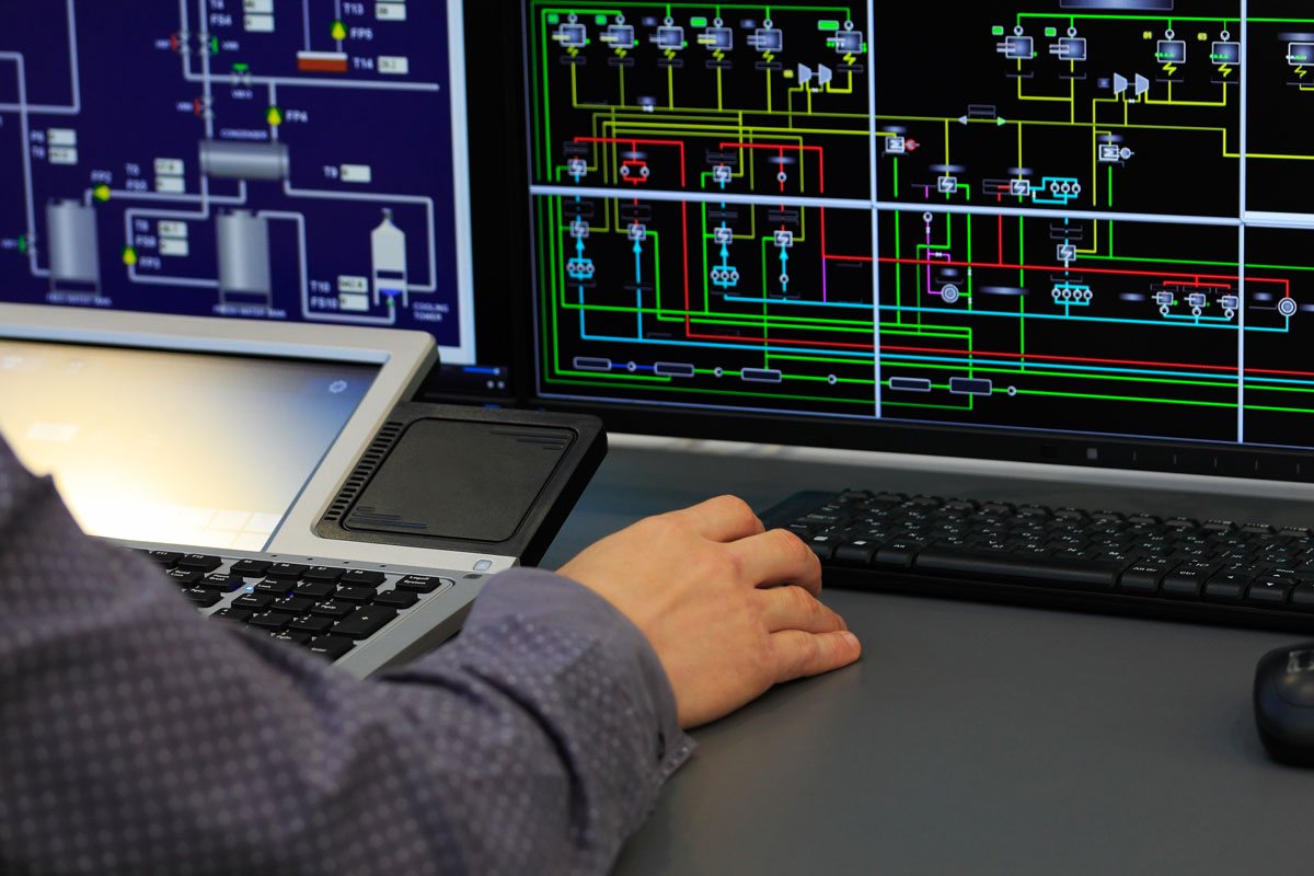 OT operator monitors industrial control systems in control room